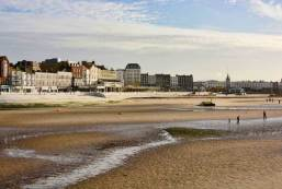 Margate town and seafront viewed from harbour wall. Kent. England. Low tide with people walking on beach