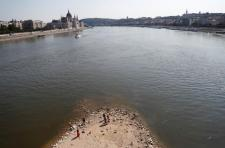 People stand on a shoal under the Margaret Bridge during the period of low water level in Budapest, Hungary, August 22, 2018. REUTERS/Bernadett Szabo